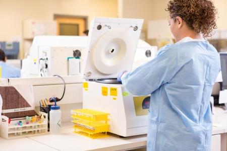pcr: Rear view of female scientist using PCR machine in laboratory