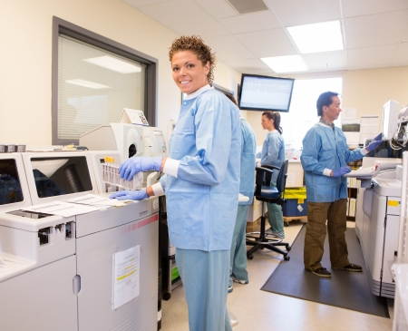 detection: Portrait of lab tech loading samples into a back up chemsitry analyzer Stock Photo
