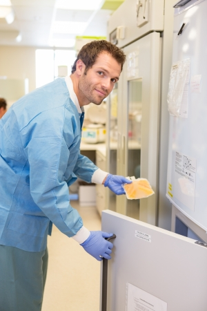 Side view of medical lab tech retrieving blood plasma from freezer photo