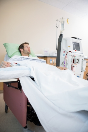 Young male patient looking away while receiving renal dialysis in hospital room photo