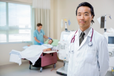 Portrait of confident doctor in hospital room with nurse checking on dialysis patient in background
