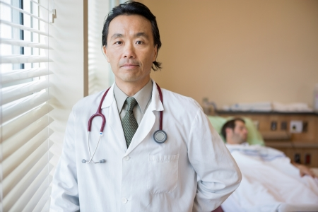 Portrait of confident male doctor with patient lying in background at hospital room photo
