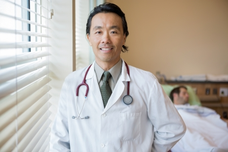 Portrait of smiling male doctor with patient in background at hospital room photo