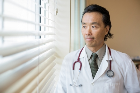 Thoughtful male doctor looking out through window in hospital room photo