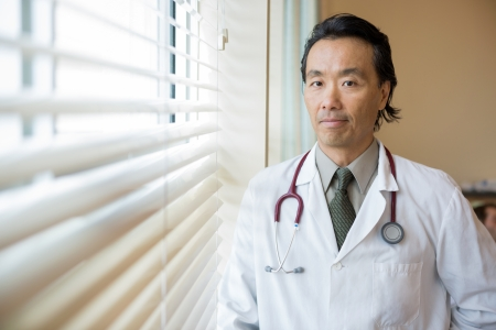 Portrait of confident male doctor with stethoscope around neck standing in hospital room photo