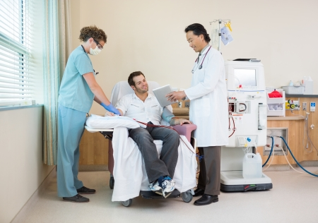 Full length of doctor showing digital tablet to patient with nurse tending to renal dialysis treatment in hospital room Stock Photo