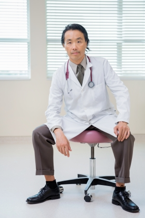 Full length portrait of Asian male cancer specialist sitting on chair in hospital room photo