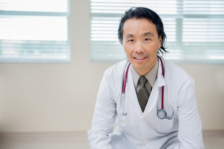 Portrait of Asian male doctor sitting in hospital room photo