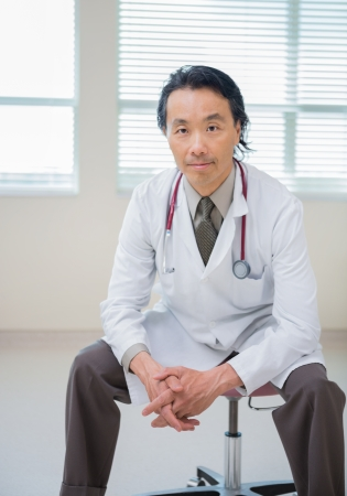 Portrait of confident male doctor with hands clasped sitting on chair in hospital room photo