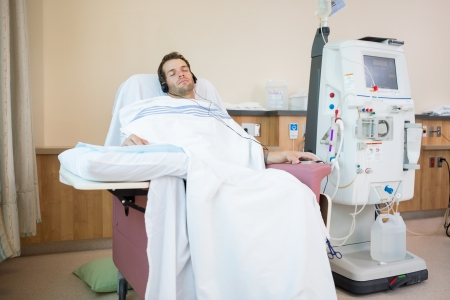 Young male patient sleeping while listening to music during renal dialysis treatment in hospital room