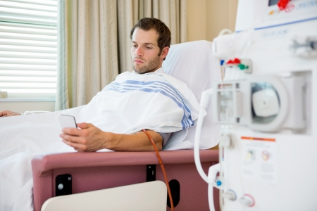 Young male patient using mobilephone at dialysis center, waiting for treatment
