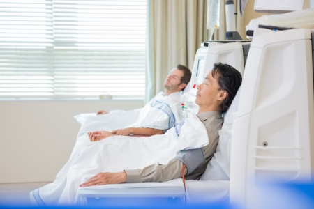 Side view of male patients undergoing renal dialysis in hospital room photo