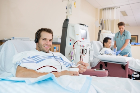 Portrait of young male dialysis patient holding glass of crushed ice during renal dialysis at hospital photo