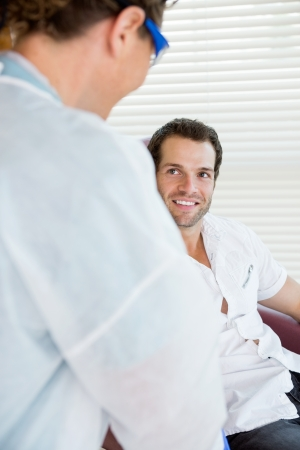 Male patient smiling at nurse in chemotherapy department of hospital photo