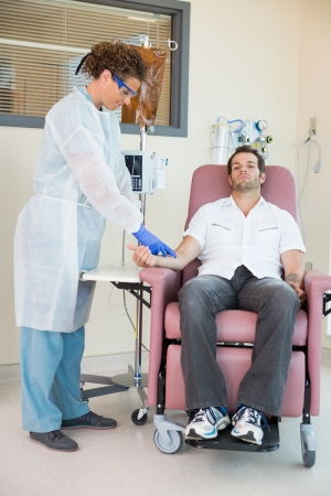 chemo: Full length of mid adult nurse injecting cancer patient during intravenous treatment in hospital room