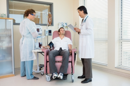 Full length of patient looking at doctor holding digital tablet in hospital room photo