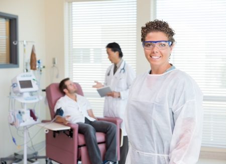 chemo: Portrait of smiling nurse with doctor examining patients heartbeat in hospital Stock Photo