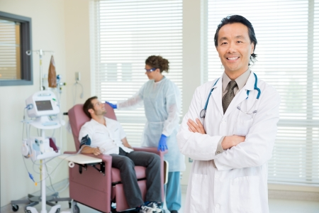 chemo: Portrait of male doctor with nurse and chemo patient in background. Stock Photo