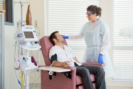 Female nurse looking at male chemo patient being monitored by heartbeat machine in hospital