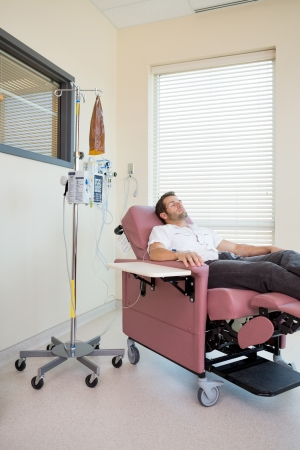 Male patient relaxing on chair during chemotherapy in hospital room photo