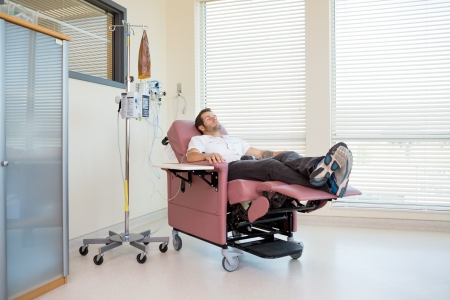Full length of male patient relaxing during chemotherapy in hospital room Stock Photo
