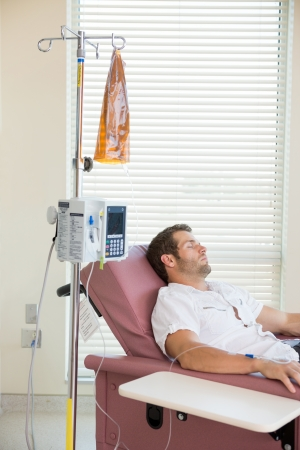 chemotherapy: Male patient sleeping while receiving chemotherapy in hospital room Stock Photo