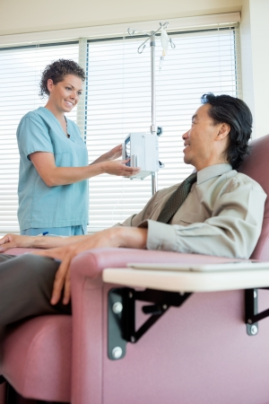 chemo: Happy female nurse looking at patient while operating IV machine for chemotherapy in hospital room