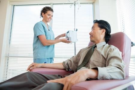 Enfermera de sexo femenino que mira al paciente mientras se ajusta la máquina IV para la quimioterapia en el cuarto de hospital