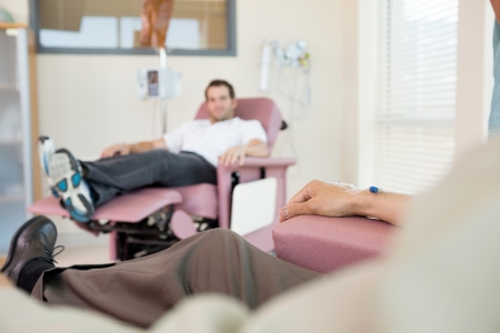 chemo: Cropped image of man with IV drip attached to his hand while patient in background at hospital room Stock Photo