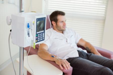 病室における化学療法中の若い男性患者の手に接続されている点滴