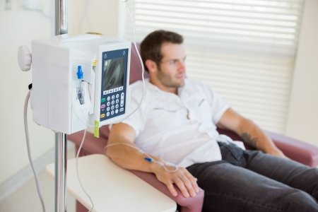 IV drip attached to young male patients hand during chemotherapy in hospital room