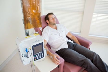 Male patient receiving chemotherapy through IV drip in hospital room