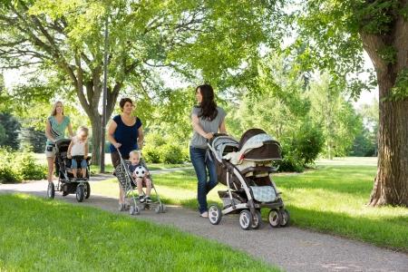 niño empujando: Madres felices con sus coches de niños caminando juntos en el parque
