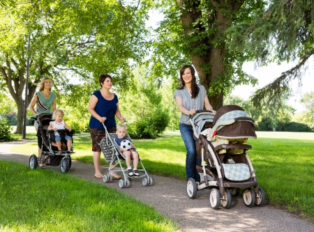 Happy mothers with their baby strollers walking together in park photo
