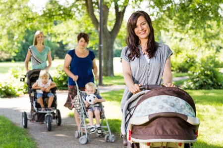 Portrait of beautiful mother pushing baby stroller in park with friends and children in background photo
