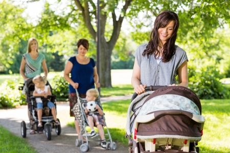 group of babies: Young mother looking at baby in stroller at park with friends and children in background Stock Photo