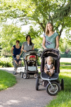 Portrait of happy mother and friends pushing baby strollers in park photo