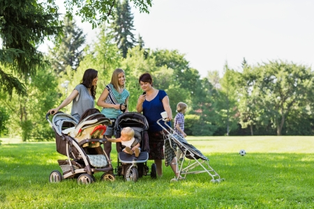 Happy mothers with baby strollers reading text message in park photo