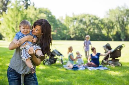 mujer hijos: Madre que lleva alegre bebé con los amigos y los niños en segundo plano en el parque