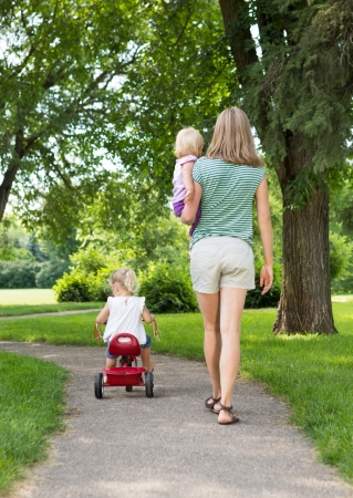 Full length rear view of mid adult mother with children strolling in park photo