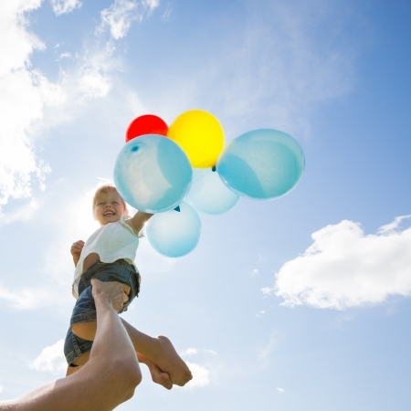 Mid adult mother lifting daughter holding colorful helium balloons against cloudy sky photo