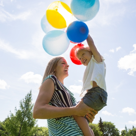 Cheerful mid adult mother and daughter playing with colorful balloons against cloudy sky photo
