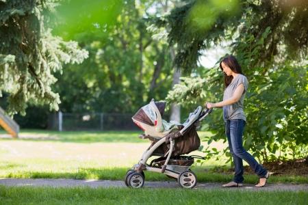 empujando: Longitud total de joven madre empujando un cochecito en el parque Foto de archivo