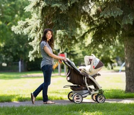 empujando: Retrato de cuerpo entero de la joven madre empujando el cochecito en el parque
