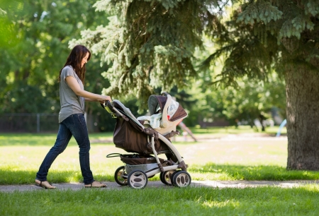 Full length side view of young mother pushing baby carriage in the park photo