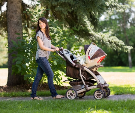 Full length of beautiful young mother pushing baby carriage in park
