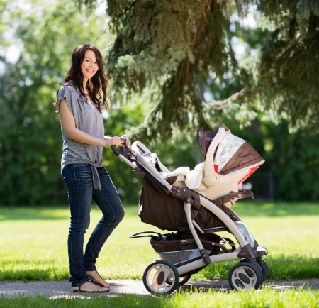 Portrait of beautiful young woman pushing baby carriage in the park photo