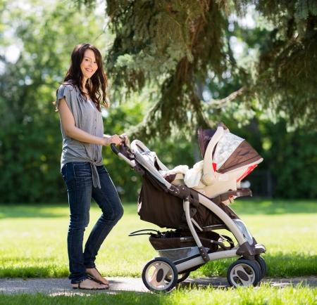 empujando: Retrato de la hermosa joven que empuja el carro de bebé en el parque Foto de archivo
