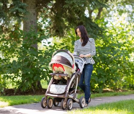 Happy young woman pushing baby carriage in park photo