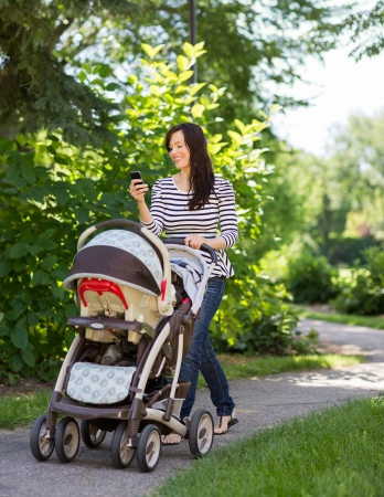 Full length of happy young woman with baby carriage using cell phone in park photo